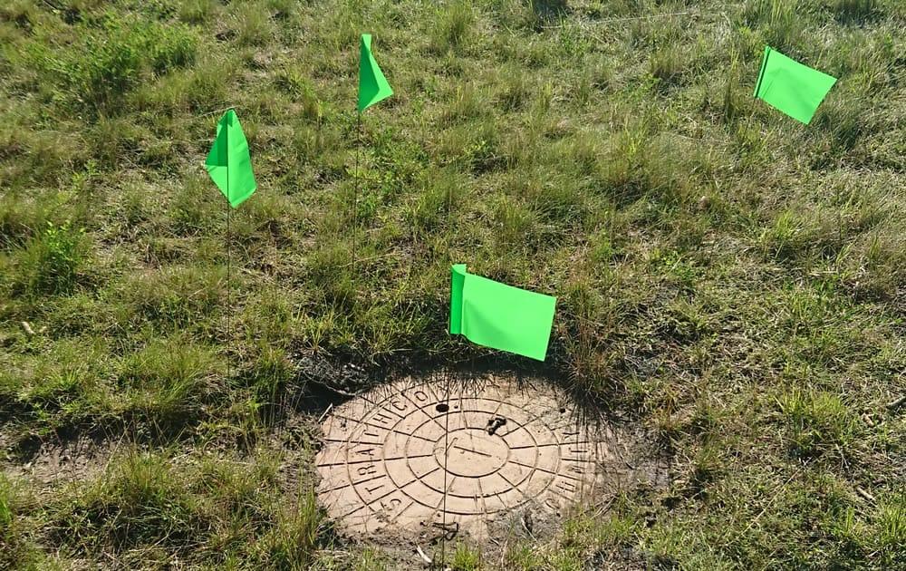 Marking storm drain in a field in Alberta